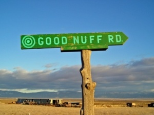"A street sign pointing into the direction of ""Good Enough"""