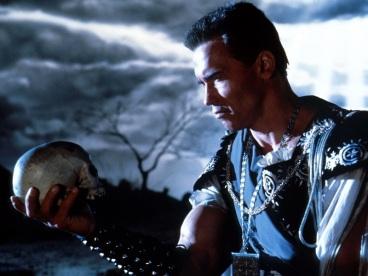 Arnold Schwarzenegger looking at a skull like Hamlet, pondering a big question.